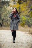 Muchacha hermosa joven con el teléfono móvil que camina en el parque Fotografía de archivo libre de regalías
