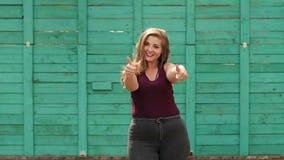 Muchacha hermosa joven con exceso de peso en el parque del verano que muestra los pulgares para arriba almacen de video