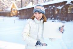 Muchacha hermosa joven con la bandera en blanco. Invierno. Foto de archivo libre de regalías