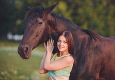 Muchacha hermosa joven con la situación del caballo del frisian Imagen de archivo libre de regalías