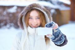 Muchacha hermosa joven con la tarjeta de visita en blanco. Invierno. Imagen de archivo libre de regalías