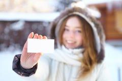 Muchacha hermosa joven con la tarjeta de visita en blanco. Invierno. Fotos de archivo