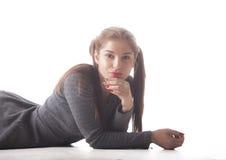 Muchacha hermosa joven con las coletas en el fondo blanco Fotos de archivo