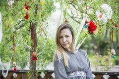 Muchacha hermosa joven con los huevos de Pascua en el árbol de Pascua del fondo Fotografía de archivo