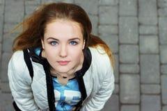 Muchacha hermosa joven con los ojos azules y el pelo rojo que camina en las calles Imagenes de archivo