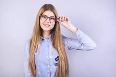 Muchacha hermosa joven con los vidrios que se colocan delante de fondo gris y que sonríen y que llevan una camisa, mucho limpio fotografía de archivo