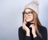 Muchacha hermosa joven con los vidrios y situación del sombrero del invierno delante del fondo gris, mucho espacio limpio fotos de archivo