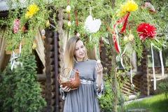 Muchacha hermosa joven con una cesta con los huevos de Pascua en el árbol de Pascua del fondo Imagen de archivo