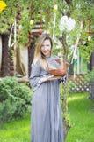 Muchacha hermosa joven con una cesta con los huevos de Pascua en el árbol de Pascua del fondo Fotografía de archivo libre de regalías