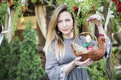 Muchacha hermosa joven con una cesta con los huevos de Pascua en el árbol de Pascua del fondo Fotos de archivo libres de regalías