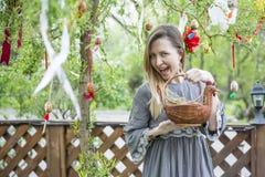 Muchacha hermosa joven con una cesta con los huevos de Pascua en el árbol de Pascua del fondo Fotos de archivo