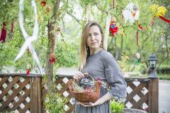 Muchacha hermosa joven con una cesta con los huevos de Pascua en el árbol de Pascua del fondo Imagen de archivo libre de regalías