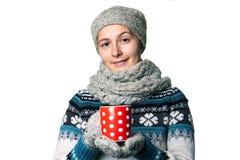 Muchacha hermosa joven con una taza en retrato del invierno de las manos en el fondo blanco, copyspace Fotos de archivo