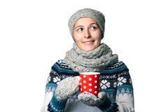 Muchacha hermosa joven con una taza en retrato del invierno de las manos en el fondo blanco, copyspace Imagen de archivo libre de regalías