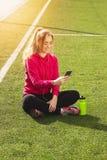Muchacha hermosa joven de la aptitud del pelo rubio que usa su teléfono en el estadio Actividad del deporte del verano Foto de archivo