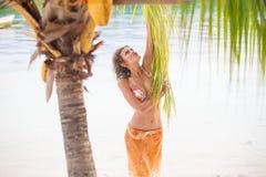 Muchacha hermosa joven de la foto que se relaja en la playa El gasto sonriente de la mujer enfría la isla al aire libre de Bali d Imagen de archivo libre de regalías