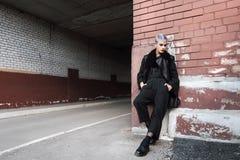 Muchacha hermosa joven de la moda que tira al aire libre cerca de la pared de ladrillo en casa Fotografía de archivo