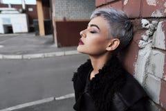 Muchacha hermosa joven de la moda que tira al aire libre cerca de la pared de ladrillo en casa Fotografía de archivo libre de regalías