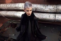 Muchacha hermosa joven de la moda que tira al aire libre cerca de la pared de ladrillo en casa Imagen de archivo libre de regalías