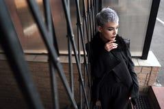 Muchacha hermosa joven de la moda que tira al aire libre cerca de la pared de ladrillo en casa Imagenes de archivo