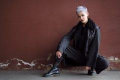 Muchacha hermosa joven de la moda que tira al aire libre cerca de la pared de ladrillo en casa Imágenes de archivo libres de regalías