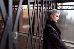 Muchacha hermosa joven de la moda que tira al aire libre cerca de la pared de ladrillo en casa Fotos de archivo libres de regalías