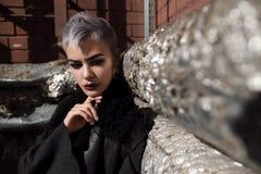 Muchacha hermosa joven de la moda que tira al aire libre cerca de la pared de ladrillo en la casa Fotos de archivo libres de regalías