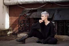 Muchacha hermosa joven de la moda que tira al aire libre cerca de la pared de ladrillo en la casa Imagen de archivo