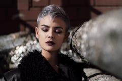 Muchacha hermosa joven de la moda que tira al aire libre cerca de la pared de ladrillo en la casa Fotografía de archivo libre de regalías