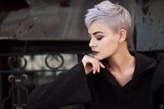 Muchacha hermosa joven de la moda que tira al aire libre cerca de la pared de ladrillo en la casa Imagen de archivo libre de regalías