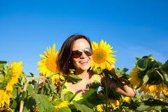 Muchacha hermosa joven de la mujer en el fondo del campo del girasol Fotos de archivo