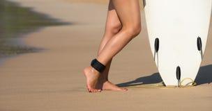 Muchacha hermosa joven de la persona que practica surf en la playa con el tablero de resaca en el brea del día Fotografía de archivo