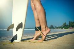 Muchacha hermosa joven de la persona que practica surf en la playa con el tablero de resaca en el brea del día Foto de archivo