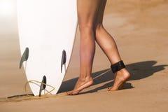 Muchacha hermosa joven de la persona que practica surf en la playa con el tablero de resaca en el brea del día Imágenes de archivo libres de regalías