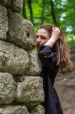 Muchacha hermosa joven del adolescente en una capa oscura y un pelo largo que mira furtivamente de detrás ruinas de una pared de  Fotografía de archivo libre de regalías