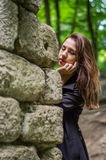 Muchacha hermosa joven del adolescente en una capa oscura y un pelo largo que mira furtivamente de detrás ruinas de una pared de  Fotos de archivo