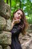 Muchacha hermosa joven del adolescente en una capa oscura y un pelo largo que mira furtivamente de detrás ruinas de una pared de  Imagen de archivo