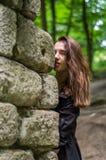 Muchacha hermosa joven del adolescente en una capa oscura y un pelo largo que mira furtivamente de detrás ruinas de una pared de  Imagenes de archivo