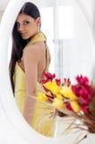 Muchacha hermosa joven del adolescente que mira su vestido en el espejo Imagen de archivo libre de regalías