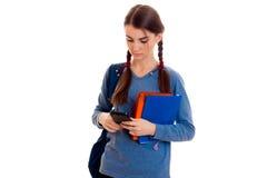Muchacha hermosa joven del estudiante con la mochila que mira su teléfono móvil y presentación aislada en el fondo blanco en estu Fotografía de archivo