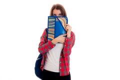 Muchacha hermosa joven del estudiante con la mochila y carpetas para la presentación de los cuadernos aisladas en el fondo blanco Imagen de archivo