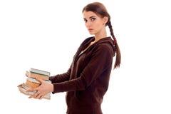 Muchacha hermosa joven del estudiante con los libros en su presentación de las manos aislados en el fondo blanco en estudio Fotos de archivo libres de regalías