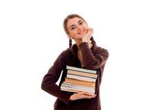 Muchacha hermosa joven del estudiante con muchos libros en su presentación de las manos aislados en el fondo blanco en estudio Foto de archivo