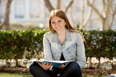 Muchacha hermosa joven del estudiante en la hierba del parque del campus con los libros que estudia el examen preparado feliz en  Fotos de archivo