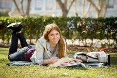 Muchacha hermosa joven del estudiante en la hierba del parque del campus con los libros que estudia el examen preparado feliz en  Fotografía de archivo