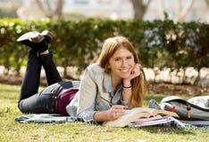 Muchacha hermosa joven del estudiante en la hierba del parque del campus con los libros que estudia el examen preparado feliz en  Fotografía de archivo libre de regalías