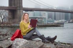Muchacha hermosa joven del estudiante que lee un libro que se sienta cerca del horizonte de New York City Imagen de archivo libre de regalías