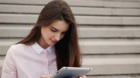 Muchacha hermosa joven del estudiante que usa una tableta afuera Lectura bastante adolescente de la mujer en el aire Foto de archivo