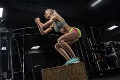 Muchacha hermosa joven del levantamiento de pesas que hace ejercicios en una GY moderna imagen de archivo libre de regalías