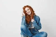 Muchacha hermosa joven del pelirrojo que sonríe mirando la cámara que se sienta en la caja sobre el fondo blanco Copie el espacio Imagen de archivo